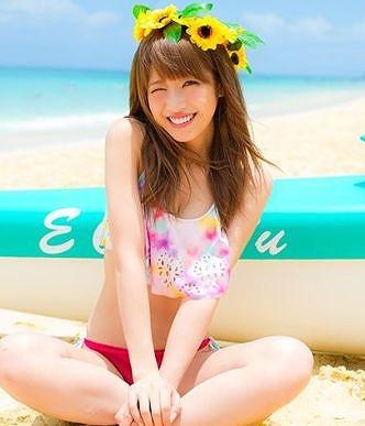 砂浜でウインクをして撮影している舟山久美子の水着画像